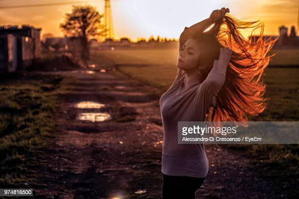 Side View Of Woman With Arms Raised Standing On Dirt Road At Sunset