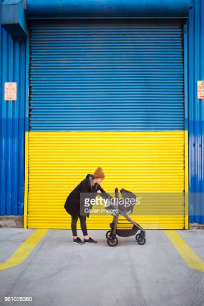 side view of woman with baby carriage on street - 乳母車 ストックフォトと画像