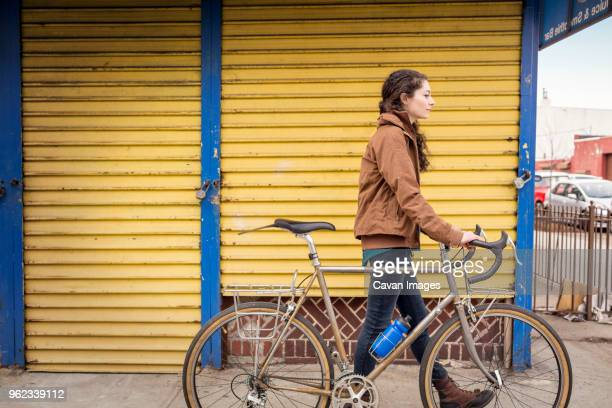 side view of woman with bicycle walking on footpath in city - yellow coat stock pictures, royalty-free photos & images
