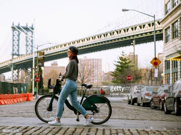Side view of woman with bike share walking on street with Manhattan Bridge in background