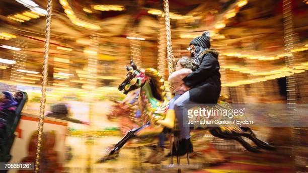 Side View Of Woman With Daughter Riding Carousel Horse At Amusement Park