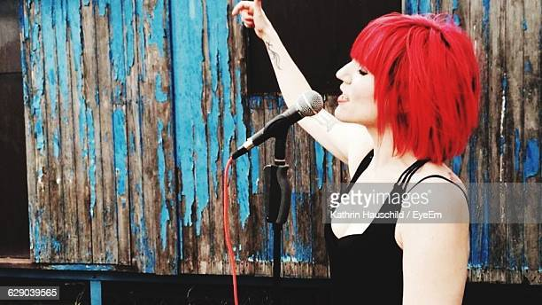 Side View Of Woman With Dyed Hair Singing Against Weathered Cottage