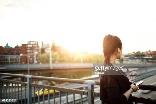Side view of woman with mobile phone standing on bridge against sky