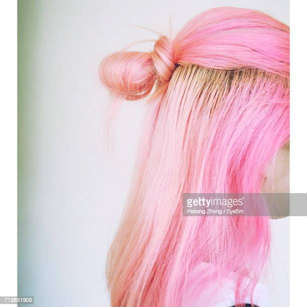 side view of woman with pink dyed hairstyle standing against white wall - pink hair stock pictures, royalty-free photos & images