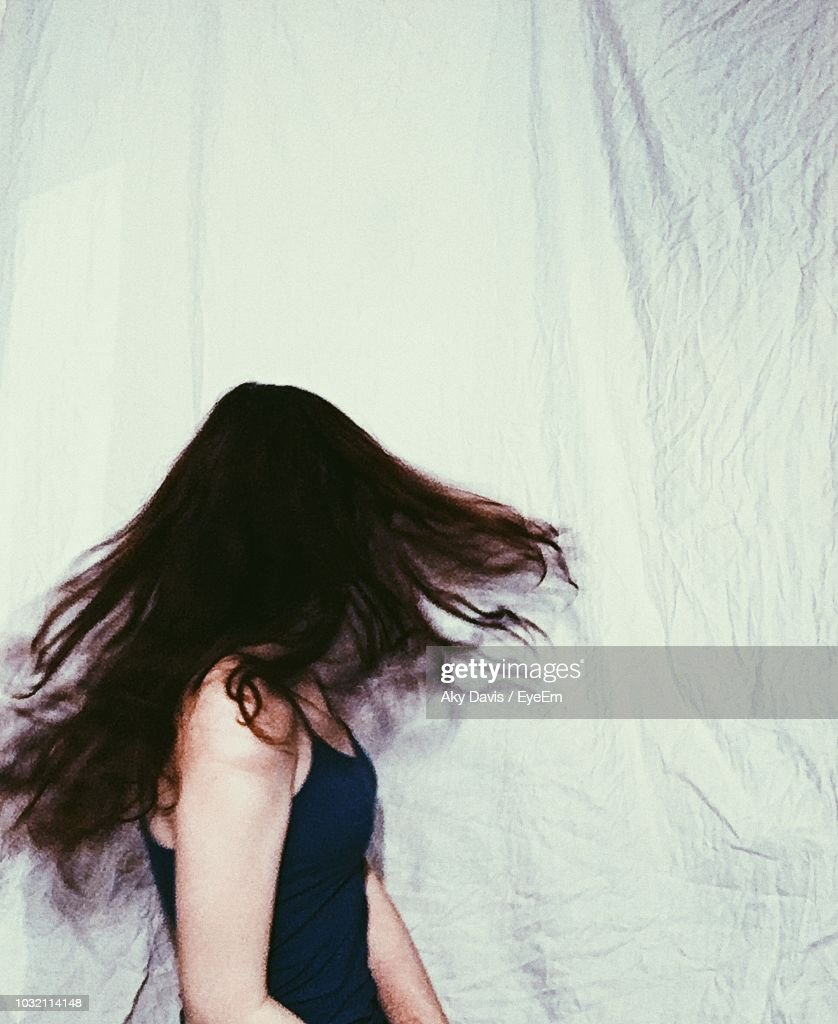 Side View Of Woman With Tousled Hair Against Curtain : ストックフォト
