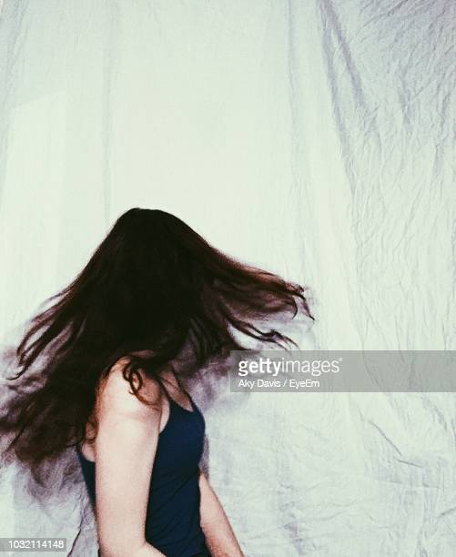 Side View Of Woman With Tousled Hair Against Curtain