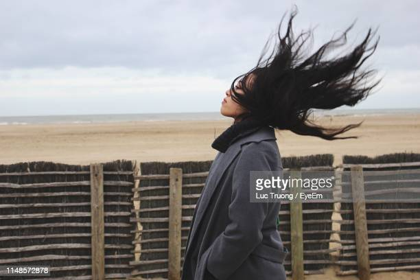 side view of woman with tousled hair at beach - overcoat stock pictures, royalty-free photos & images
