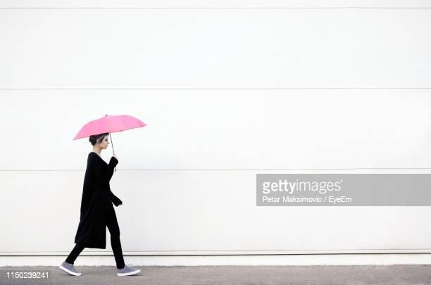 side view of woman with umbrella walking on road against wall - 傘 ストックフォトと画像