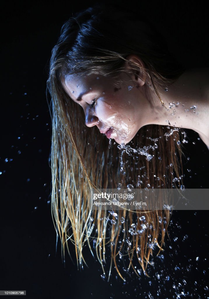 side view of woman with water on face against black background