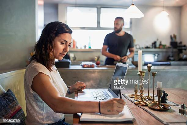 Side view of woman working at dining table while man standing in background