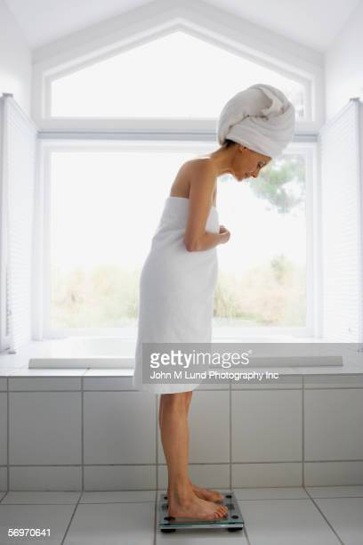 Side view of woman wrapped in towel standing on scale