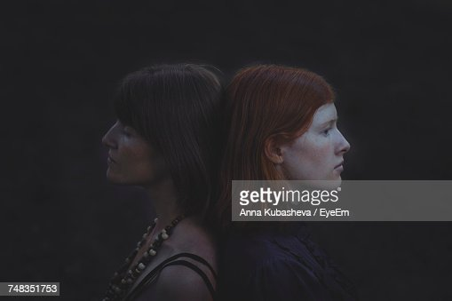 Side View Of Women Against Black Background