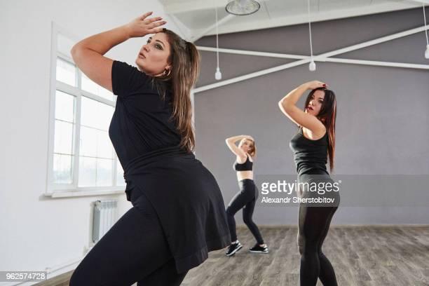 Side view of women dancing in studio
