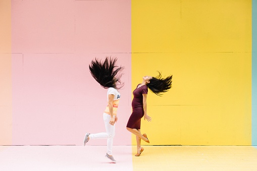 Side View Of Women Dancing While Standing Against Colored Wall - gettyimageskorea