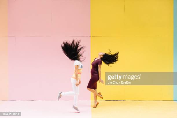 side view of women dancing while standing against colored wall - kleurenfoto stockfoto's en -beelden
