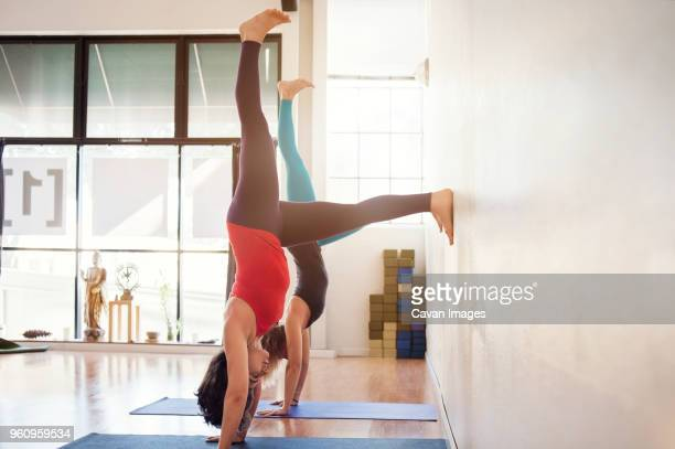 Side view of women doing handstand exercise by wall in gym