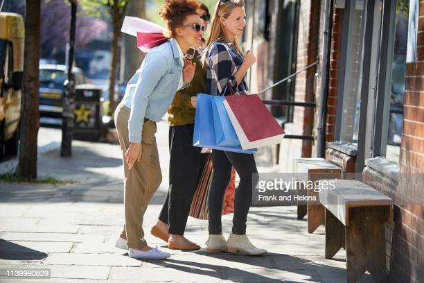 side view of women holding shopping bags standing in street looking in shop window - helena price stock-fotos und bilder