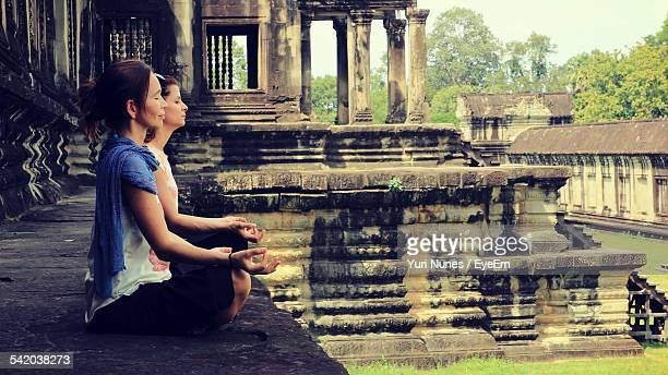 Side View Of Women Meditating Outside Temple