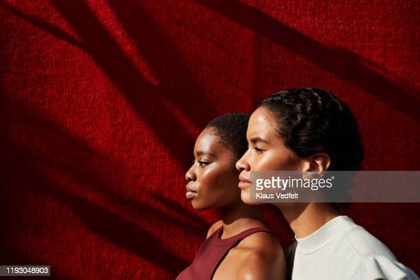 side view of women standing against red wall - alleen vrouwen stockfoto's en -beelden