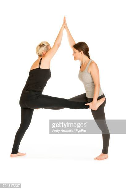 Side View Of Women Stretching While Representing Letter A Against White Background