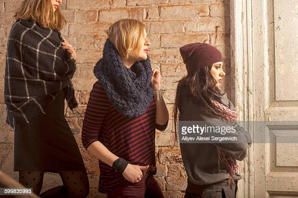 Side view of women wearing knitwear standing on stairs in front of brick wall looking away