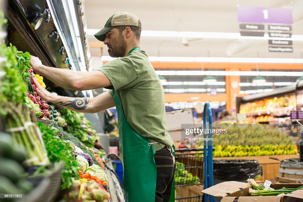 Side view of worker arranging vegetables on shelves at supermarket : Stock Photo