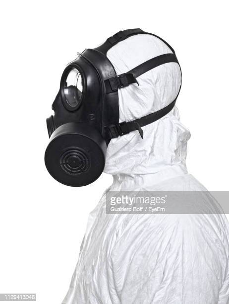 side view of worker in protective workwear standing against white background - gas mask stock pictures, royalty-free photos & images