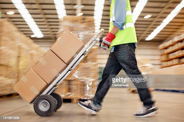 Side view of worker pushing trolley of cardboard boxes through warehouse