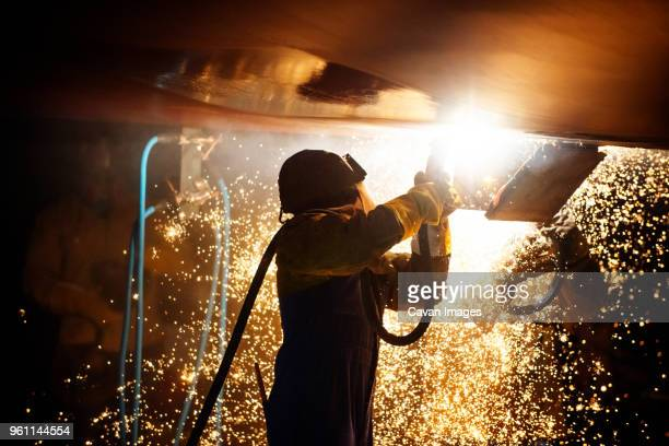 side view of worker welding airplane wing at night - welding stock photos and pictures