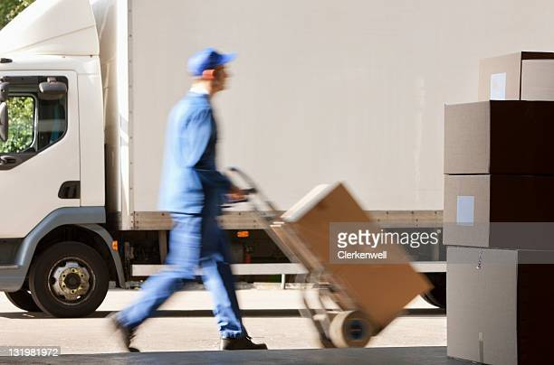 Side view of worker with push cart outside warehouse