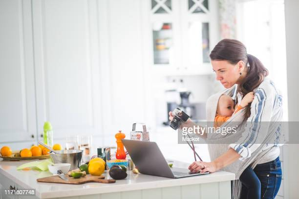 side view of working mother food blogging while breastfeeding daughter in baby carrier at kitchen - camera icon stock pictures, royalty-free photos & images
