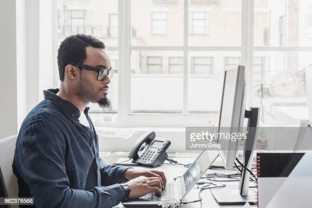 Side view of young African man using laptop computer in modern office