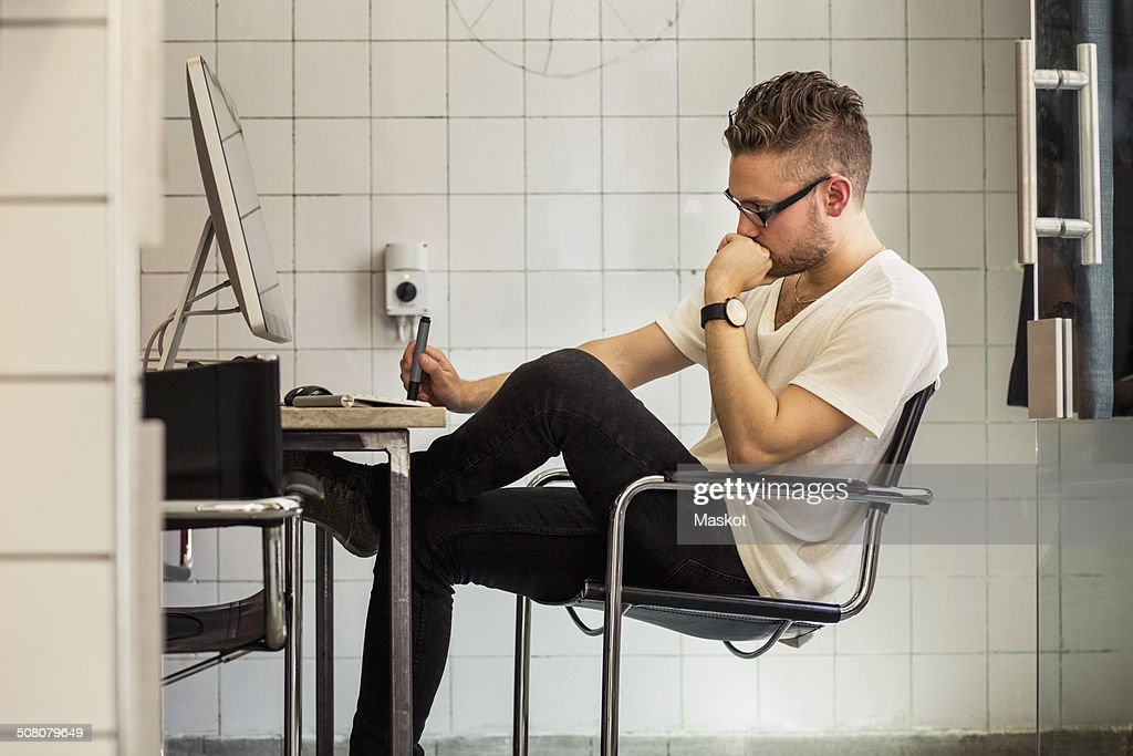 Side view of young businessman at computer desk in new office : Stock Photo