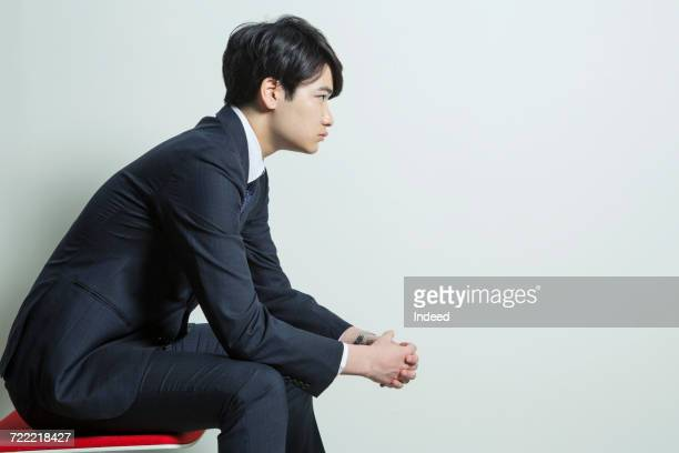 Side view of young businessman sitting on chair