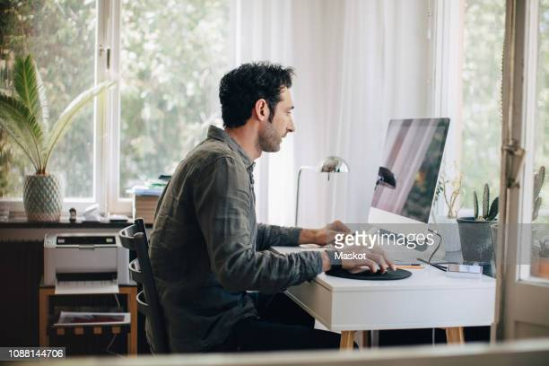 side view of young businessman using computer while sitting at desk in home office - personal computer foto e immagini stock