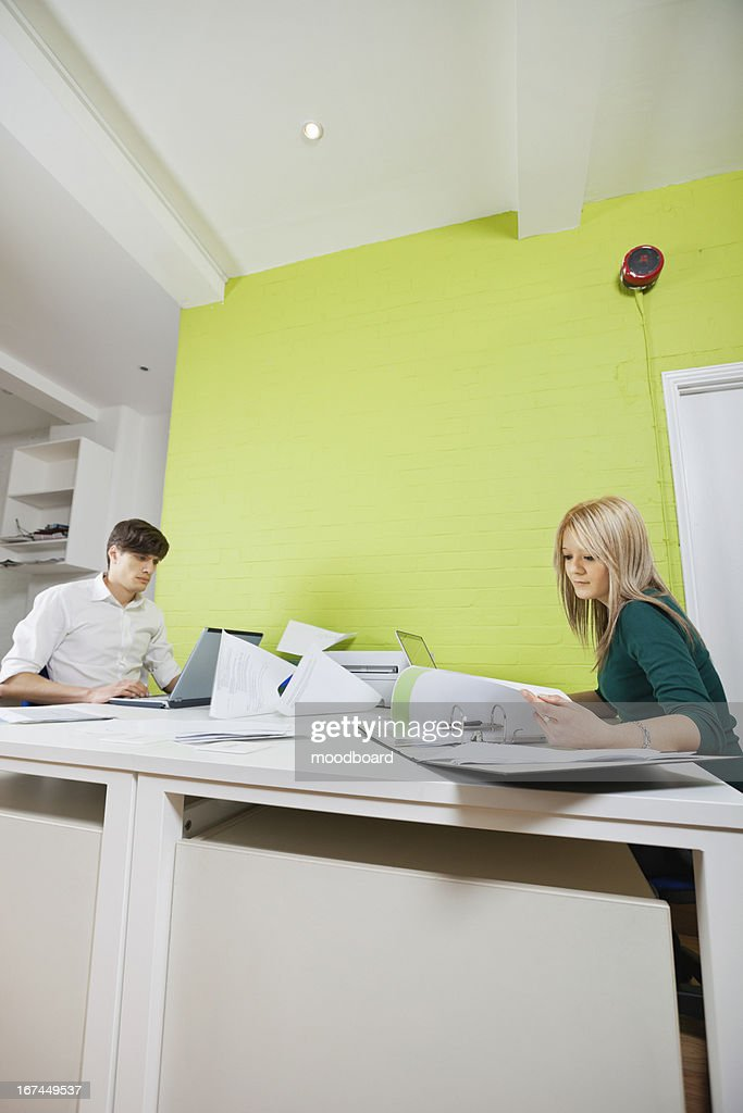 Side view of young businesspeople busy working at desk : Stock Photo