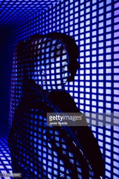 side view of young confident woman standing against projection screen. she is lighted with squared neon code. - google stock pictures, royalty-free photos & images