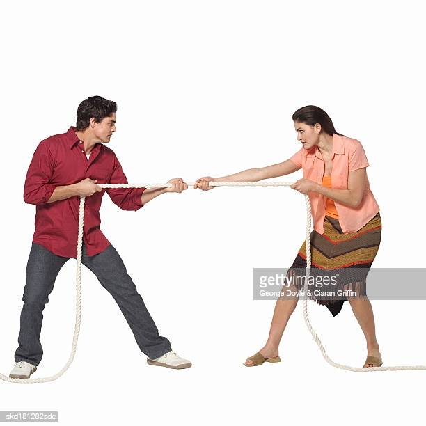 Side view of young couple pulling rope