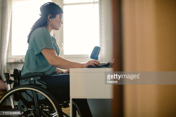 side view of young disabled freelance worker using computer at desk in room - assistive technology stock photos and pictures