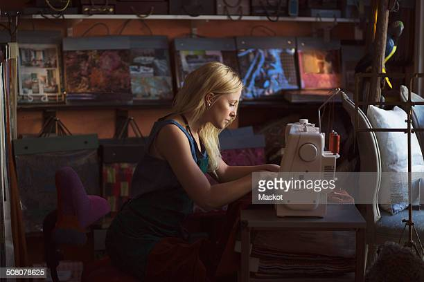 Side view of young fashion designer using sewing machine in studio
