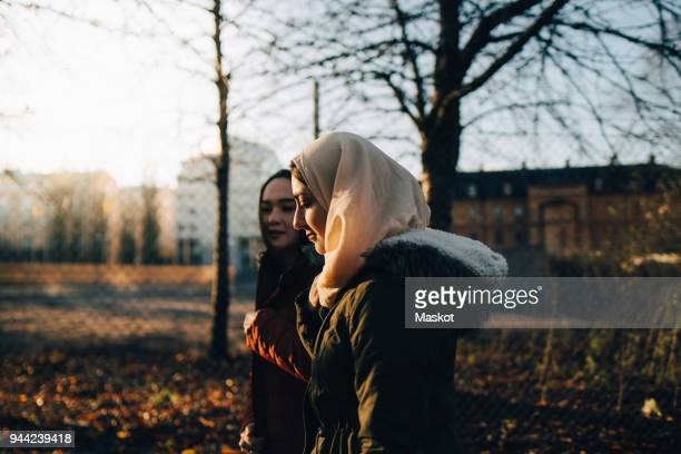 Side view of young female Muslim friends walking in city during sunset
