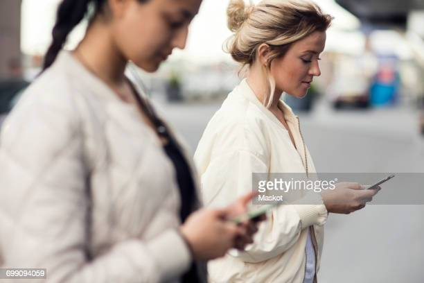 Side view of young females using mobile phones in city