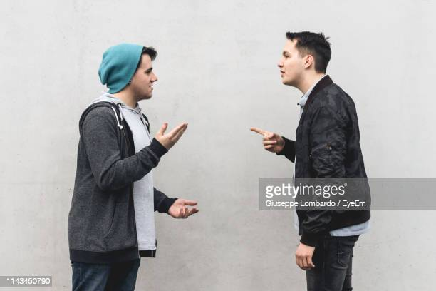 side view of young friends arguing while standing by wall - conflict stockfoto's en -beelden