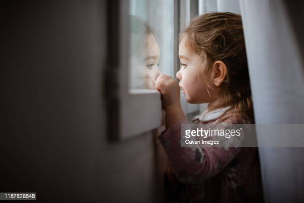 side view of young girl looking outside window at rain - bambine femmine foto e immagini stock