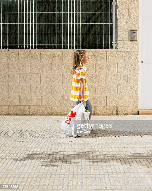 side view of young girl (4-6) walking on pavement with shopping bag, alicante, spain, - dragging stock pictures, royalty-free photos & images