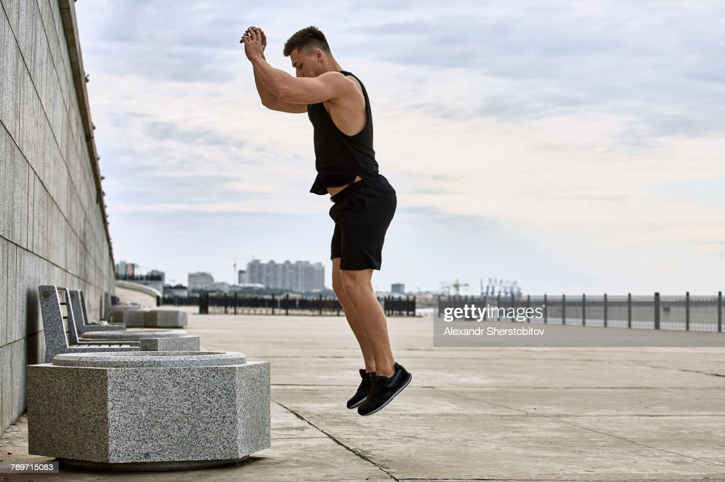 Side view of young male athlete jumping on footpath against sky, Blagoveshchensk, Amur, Russia : Stock Photo