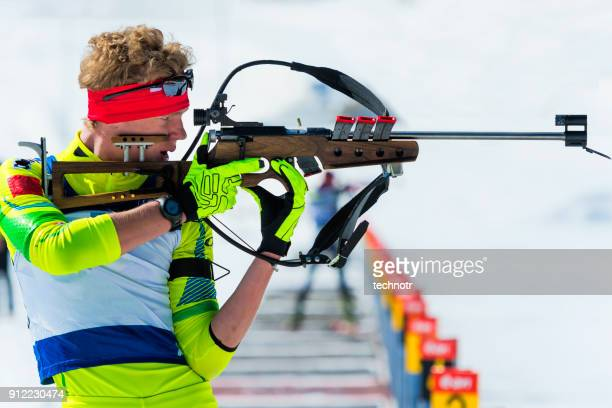 Side View of Young Male Biathlon Competitor Practicing at Shooting Range, Standing Position
