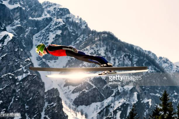 side view of young male ski jumper in mid-air, sun reflection - ski jumping stock pictures, royalty-free photos & images