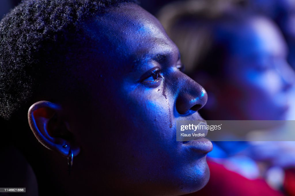 Side view of young man crying while watching movie in cinema hall : Stock Photo