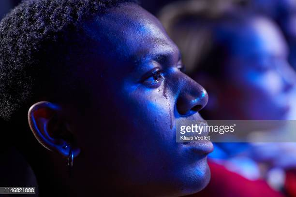 side view of young man crying while watching movie in cinema hall - film industry stock pictures, royalty-free photos & images